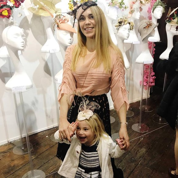 Judith Countess Kinsky and Maxima Countess Kinsky posing at London Hat Week Worldgarden 2019 exhibition. THe peach hat displayed at the back is from JMK MILLINERY, Judith is also the curator of Palma Hat Week 2019